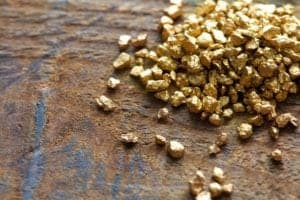 Gold nuggets on a wood table.