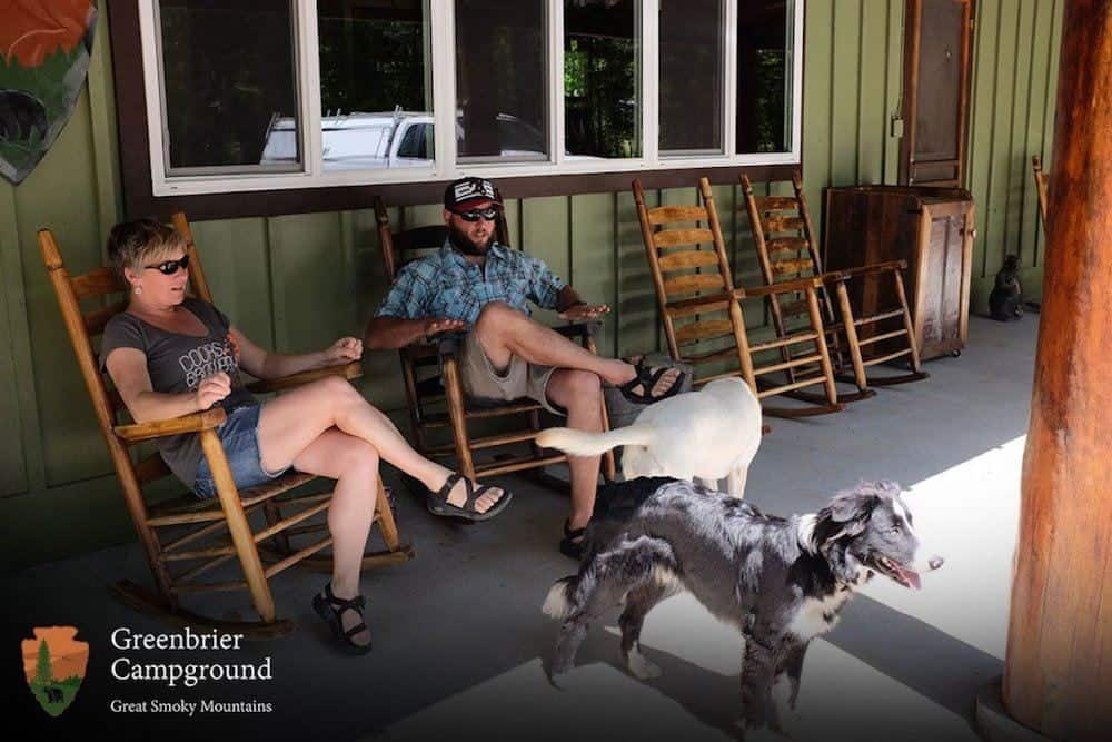 Guests and their dogs relaxing in rocking chairs at Greenbrier Campground in the Smokies.