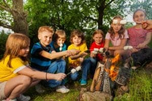 Kids making s'mores around a campfire