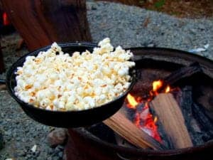 popcorn in a pan next to fire